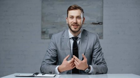 Photo for Bearded businessman in suit talking while looking at camera in office - Royalty Free Image