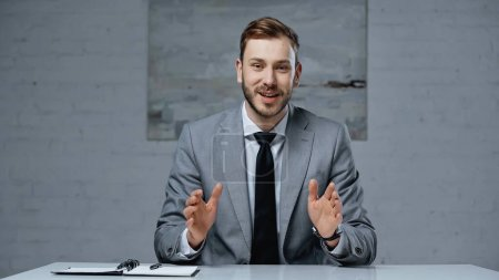 businessman in suit talking while gesturing during interview in office