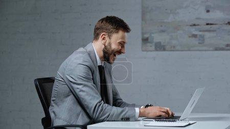 Photo pour Vue latérale de barbu homme d'affaires riant tout en utilisant un ordinateur portable au bureau - image libre de droit