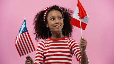 cheerful african american girl holding flags of america and canada isolated in pink