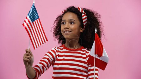 smiling african american girl holding flags of america and canada isolated in pink