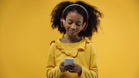 Photo for Curly african american girl in headphones using smartphone isolated on yellow - Royalty Free Image