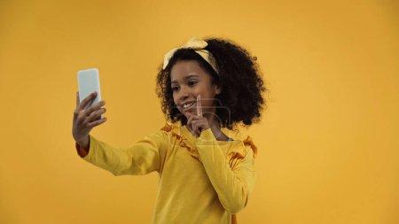 Photo pour Gai afro-américain fille prendre selfie isolé sur jaune - image libre de droit