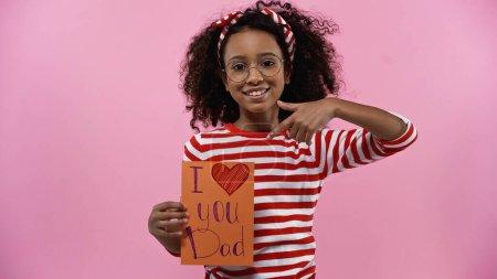 Photo pour Heureux afro-américaine fille dans des lunettes pointant du doigt à la carte de vœux avec je t'aime papa lettrage isolé sur rose - image libre de droit