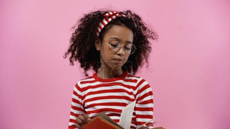 curly african american girl in glasses reading novel isolated on pink