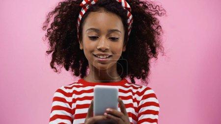 Photo pour Heureux afro-américain fille textos sur smartphone isolé sur rose - image libre de droit