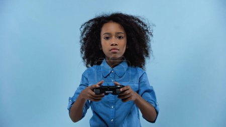 KYIV, UKRAINE - MARCH 02, 2021: curly african american girl holding gamepad isolated on blue