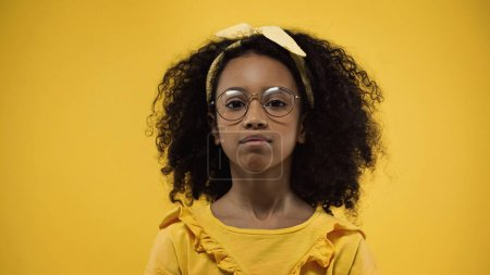 curly african american girl in glasses looking at camera isolated on yellow