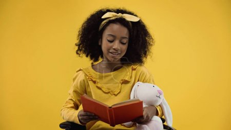 happy african american girl with soft toy reading book isolated on yellow