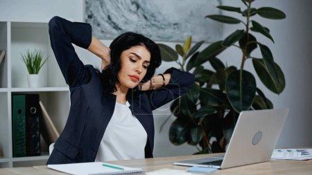 Photo pour Femme d'affaires fatiguée étirant près d'un ordinateur portable dans le bureau - image libre de droit