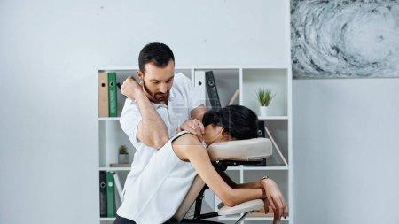 Masseur macht Rückenmassage für Geschäftsfrau im Büro