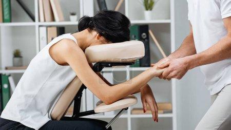 Masajista haciendo masaje de manos a empresaria en silla de masaje en oficina