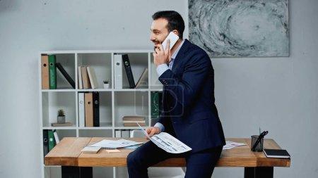 Photo pour Homme d'affaires joyeux parlant sur smartphone et tenant du papier avec des graphiques dans le bureau - image libre de droit