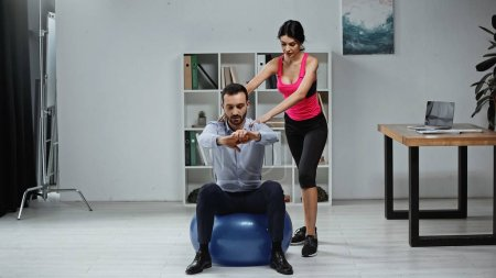 Fitness trainer standing near businessman on fitness ball in office