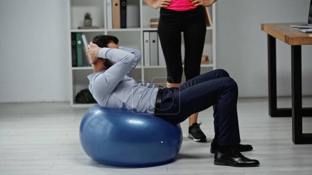 Fitness trainer standing near businessman training on fitness ball in office