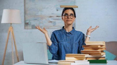 Photo for Young woman in glasses with book on head near laptop on desk - Royalty Free Image