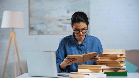 mujer joven en gafas libro de lectura cerca del ordenador portátil en el escritorio