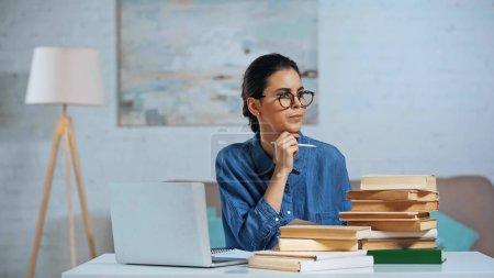 Foto de Mujer joven pensativa sosteniendo lápiz y mirando hacia otro lado cerca de la computadora portátil y libros en el escritorio - Imagen libre de derechos