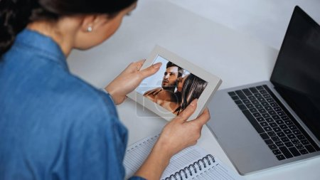 Photo for Young woman holding photo frame with picture near laptop - Royalty Free Image