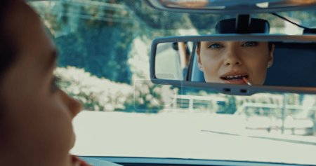 blurred and happy woman applying lip gloss while looking in rearview mirror