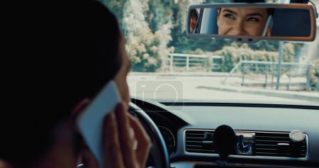 happy woman driving car and talking on smartphone