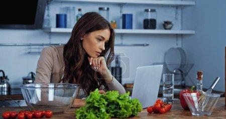 attraktive Frau sucht Rezept in Laptop neben Zutaten auf Tisch
