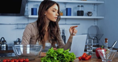 Foto de Mujer joven señalando con el dedo cerca del ordenador portátil y los ingredientes en la mesa - Imagen libre de derechos