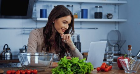 Foto de Mujer feliz búsqueda receta en el ordenador portátil cerca de los ingredientes en la mesa - Imagen libre de derechos