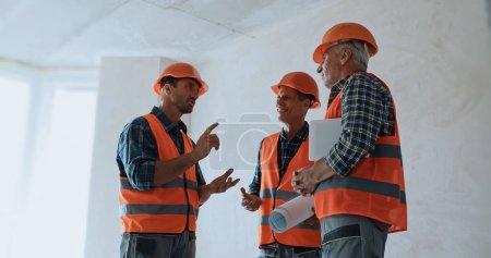 Photo pour Geste constructeur tout en parlant avec des collègues sur le chantier de construction - image libre de droit