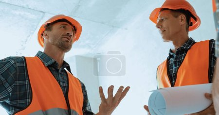 Photo pour Constructeur en hard hat geste tout en parlant sur le chantier de construction - image libre de droit