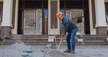 Photo pour Constructeur creuser terrain avec pelle près de la construction sur le site de construction - image libre de droit