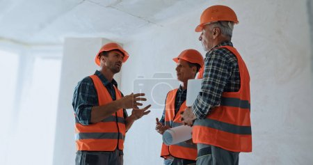 Builder gesturing while talking with coworkers in hard hats on construction site