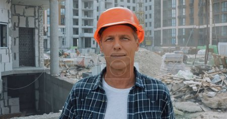 builder in hard hat smiling at camera on construction site