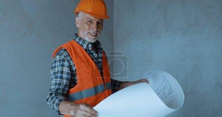 Photo pour Heureux constructeur tenant le plan et souriant sur le chantier de construction - image libre de droit