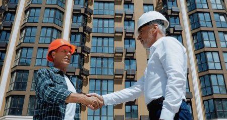 Photo for Engineer and builder shaking hands and talking on construction site - Royalty Free Image
