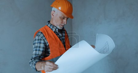 Photo for Happy builder looking at blueprint on construction site - Royalty Free Image