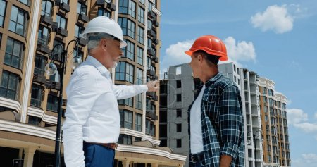 Photo for Mature engineer pointing with finger near builder on construction site - Royalty Free Image