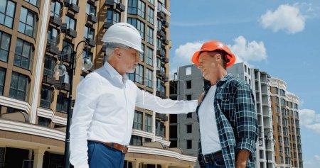 Photo pour Ingénieur mature touchant épaule du constructeur sur le chantier de construction - image libre de droit
