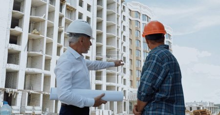 Engineer with blueprints pointing with hand while talking with builder on construction site