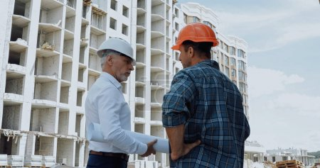Engineer with blueprints talking with builder standing with hand on hip on construction site