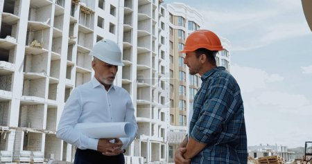 Engineer with blueprints having conversation with builder on construction site