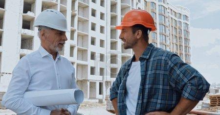 Ingenieur mit Bauplänen im Gespräch mit glücklichem Bauherrn auf Baustelle