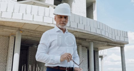 mature engineer holding eyeglasses on construction site