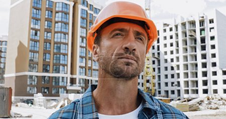 Photo for Handsome builder looking away on construction site - Royalty Free Image