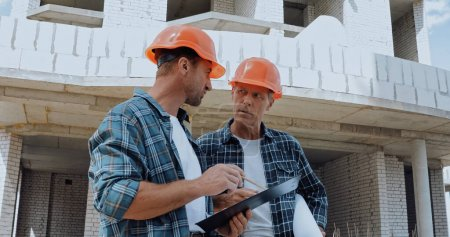 Builders looking at each other and talking on construction site
