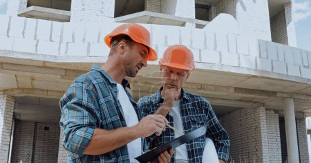 Builders looking at clipboard and talking on construction site
