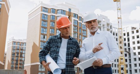 Photo for Mature engineer and builder with gadget and blueprint talking on construction site - Royalty Free Image