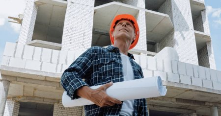 low angle view of mature builder holding blueprint and smiling on construction site