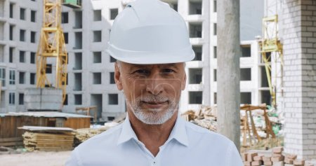 Photo for Smiling engineer looking at camera near building on background - Royalty Free Image