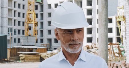 Photo for Smiling engineer looking away near building on background - Royalty Free Image
